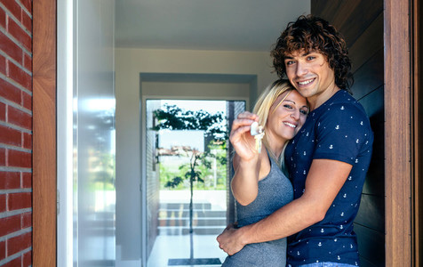 Couple showing the keys of their house