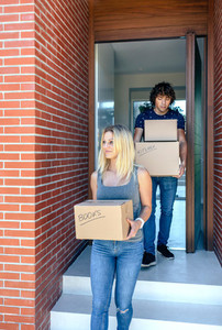 Couple moving carrying cardboard boxes