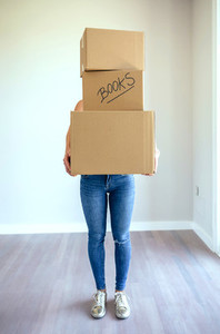 Unrecognizable woman carrying moving boxes