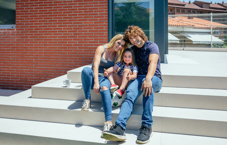 Parents and son in front of new home