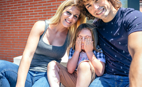 Parents and shy son in front of new home