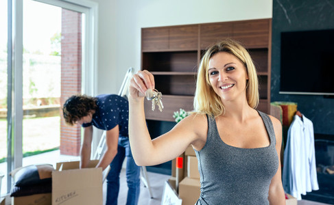 Woman showing keys while her husband unpacks