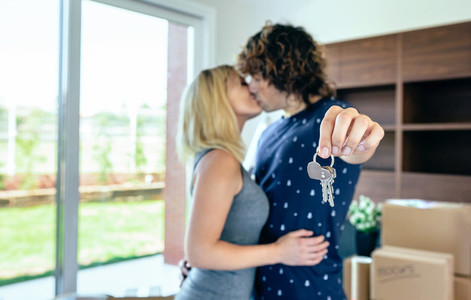 Moving couple kissing and showing keys
