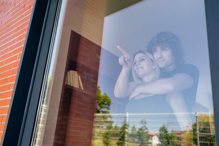 Couple looking at the garden through the window