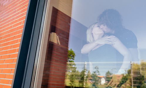 Couple kissing behind the window