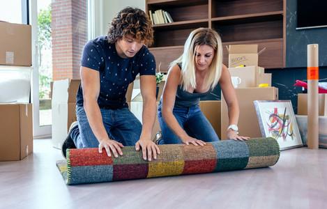 Couple unrolling the carpet