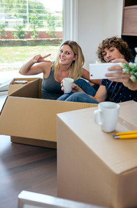 Couple making selfie sitting inside moving box