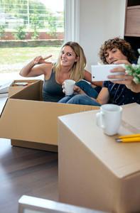 Couple making selfie sitting inside moving box