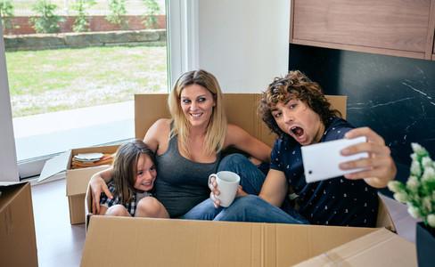 Family making selfie sitting inside moving box