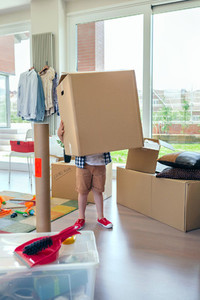 Boy carrying very large moving box