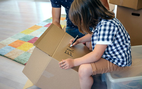 Boy writing in a moving box