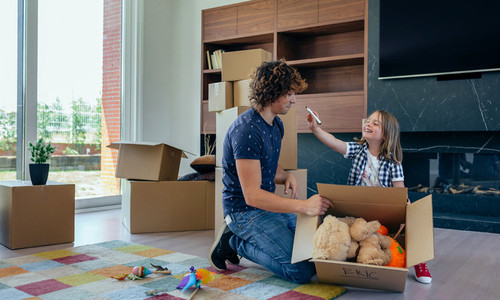 Child playing with father preparing moving boxes