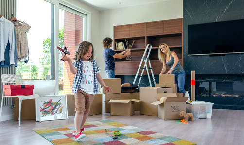Boy playing with toy airplane while parents unpack