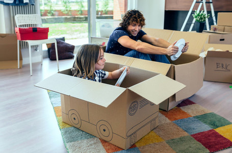 Father and son playing car racing with cardboard boxes