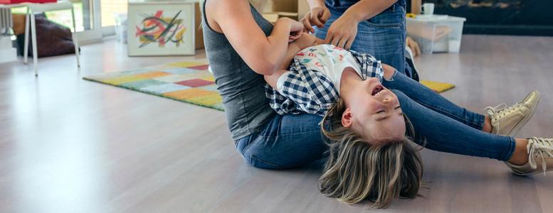 Parents tickling their son