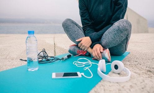 Low section of woman sitting with sport accessories
