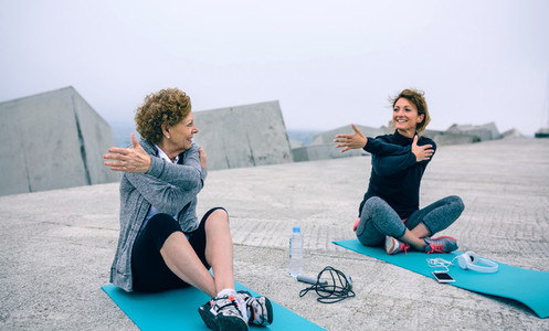 Senior woman stretching with female coach