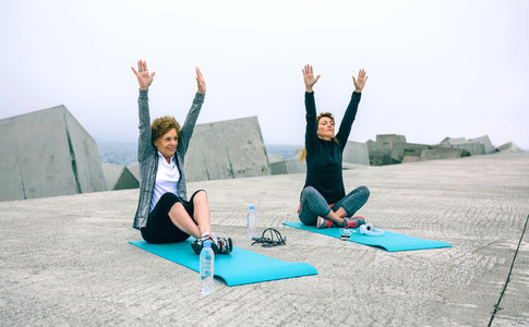 Senior woman stretching arms with coach