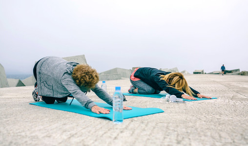 Unrecognizable young and senior woman stretching back outdoors