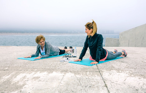 Senior woman with female coach stretching back