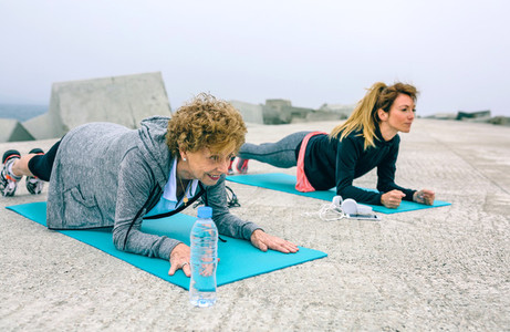 Senior woman and coach doing plank exercise