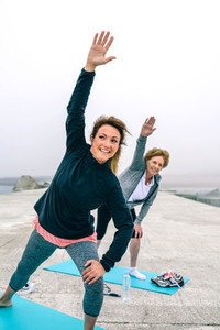 Personal trainer with senior woman with stretching side