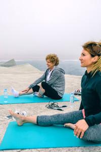 Senior woman stretching legs with female coach