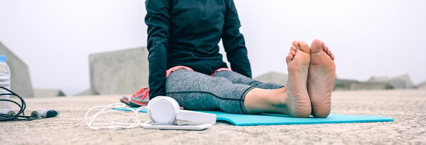 Unrecognizable woman exercising on mat