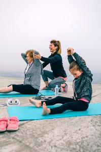 Women exercising with little girl