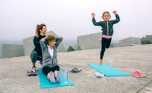 Girl jumping while women train