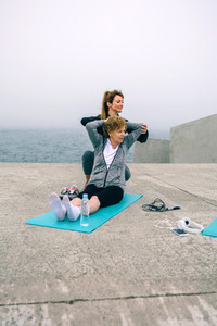 Young woman exercising with senior woman
