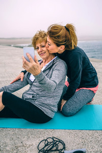 Senior woman taking selfie with her daughter