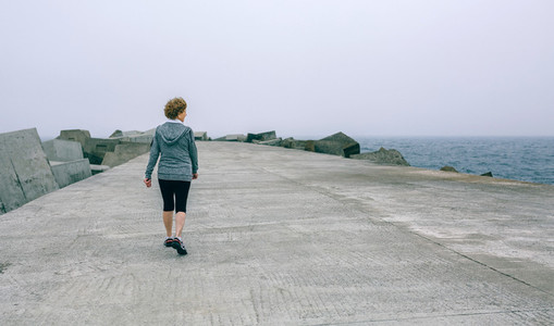 Back view of woman walking by sea pier
