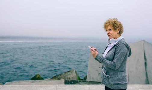 Senior sportswoman using her smartphone