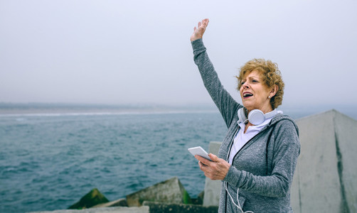 Senior sportswoman using smartphone and waving