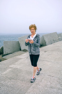 Senior sportswoman walking and looking at her smartphone