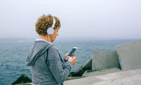Unrecognizable senior sportswoman using her smartphone
