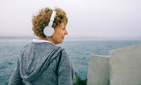 Senior sportswoman with headphones looking aside
