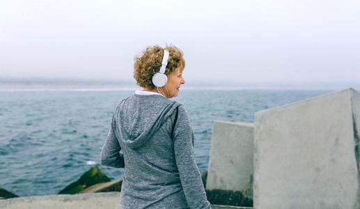 Senior sportswoman with headphones looking aside