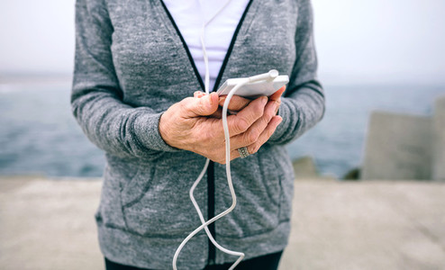 Senior sportswoman holding her smartphone