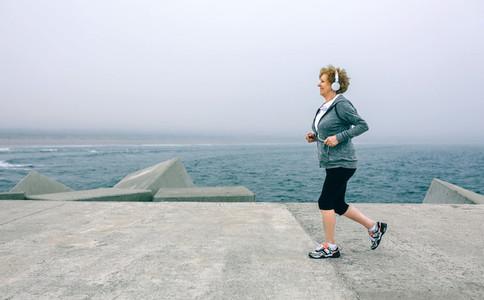 Senior sportswoman with headphones running