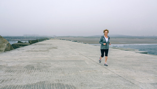 Senior sportswoman with headphones running