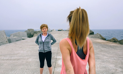Woman stretching with senior woman