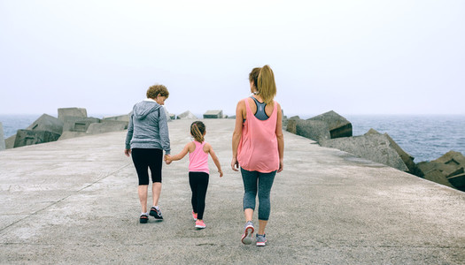 Back view of three female generations walking