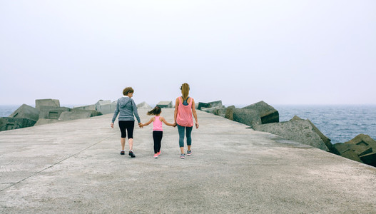 Back view of three female generations walking