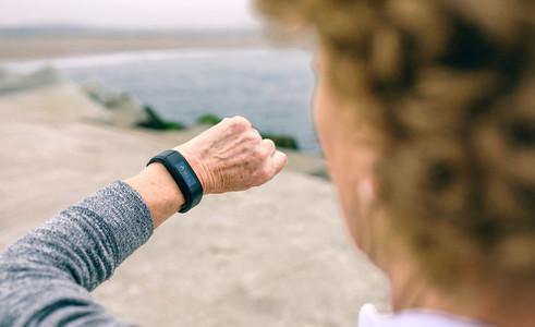 Senior woman looking smart watch