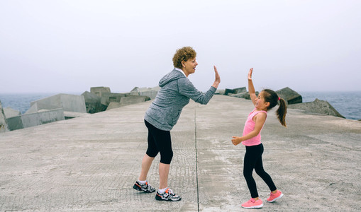 Senior sportswoman and little girl high five