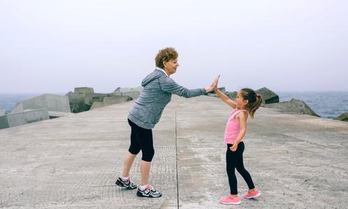 Senior sportswoman and little girl high five