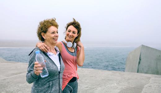 Two women walking by sea pier