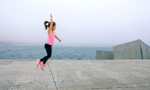 Little girl jumping by sea pier